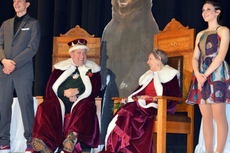 Saranac Lake Winter Carnival King John Wamsganz and Queen Anita Meserole share a smile on their thrones in front of a large bear cutout at Friday night's Coronation. Beside them are Saranac Lake High School seniors Joseph Viscardo and Alivia Sapone, the Winter Carnival Court's attendants to the queen and king. (Enterprise photos — Antonio Olivero)