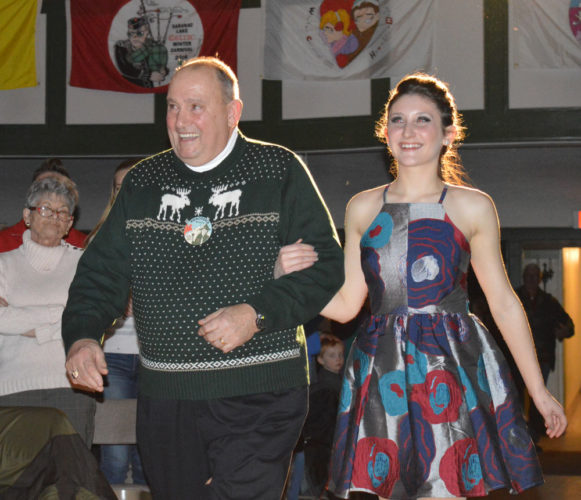Saranac Lake Winter Carnival King John Wamsganz is escorted to the stage by Attendant to the King Alivia Sapone of Saranac Lake High School at Friday night's Coronation. (Enterprise photo — Antonio Olivero)