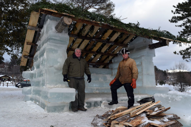 Brian McDonnell, left, and John Pietras, have built an ice lean-to near the Saranac Lake Winter Carnival Ice Palace.  (Enterprise photo — Chris Knight)