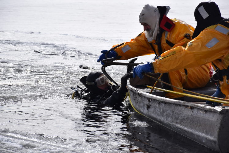 Wayne LaPierre, in SCUBA gear, swims in the frigid water of the Raquette River in Tupper Lake Saturday to try to hook one of two machines that had gone through the ice earlier that morning. (Enterprise photo — Justin A. Levine)