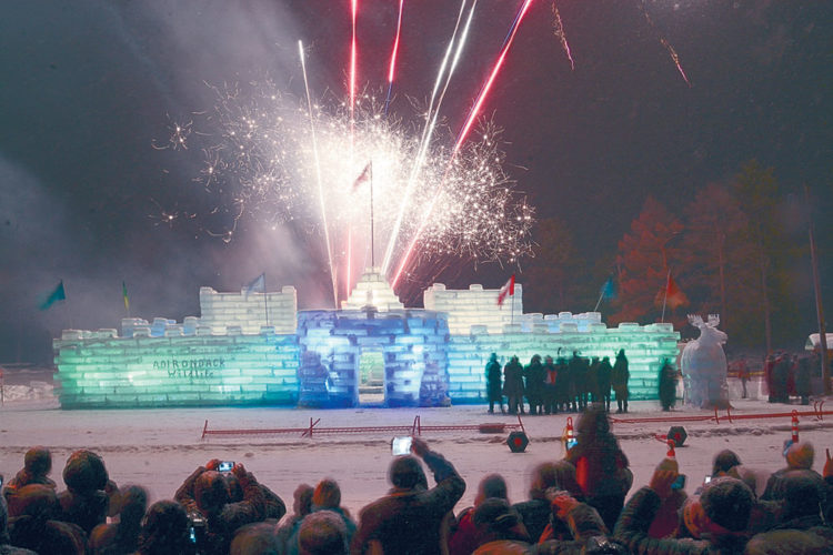 Fireworks soar skyward during Saturday's lighting of the 2017 Saranac Lake Winter Carnival Ice Palace. The carnival royalty can be seen standing in a group next to the palace. (Enterprise photo — Lou Reuter)