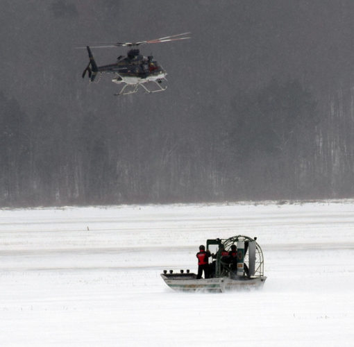 A state police helicopter and a rescue air boat prepare to pull a body from frozen Raquette Pond Monday in Tupper Lake. (Enterprise photo — Justin A. Levine)