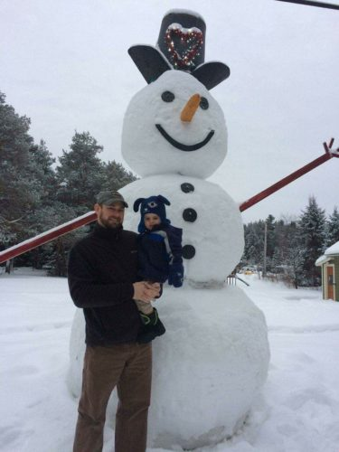 Pat McCormick and his son Elliot stand next to the giant snowman they built in their yard on Route 3 in Vermontville. It stands nearly 12 feet tall. (Photo — Amy McCormick)