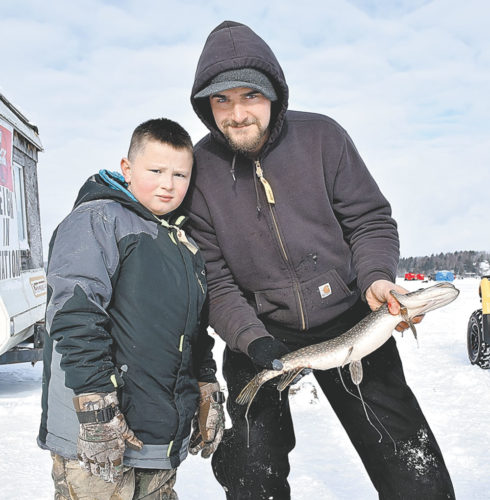 Keith Kathan, right, and Aiden Martell of Northville show off a 2.2-pound northern pike they caught during the annual Northern Challenge Ice Fishing Derby on Lake Simon Saturday in Tupper Lake. (Enterprise photo — Justin A. Levine)