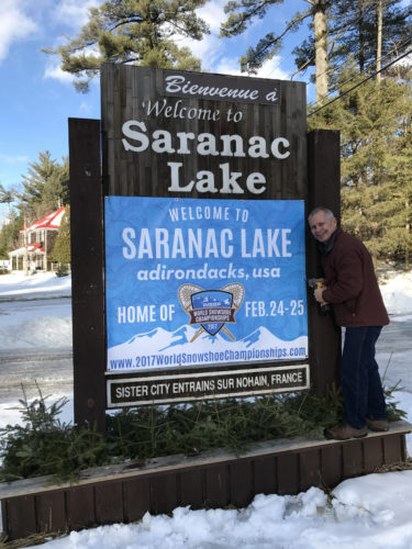 Saranac Lake Mayor Clyde Rabideau finishes installing a sign Wednesday on state Route 3 near Dewey Mountain Recreation Center. This is one of four signs outside the village touting the upcoming World Snowshoe Championships Feb. 24-26. Other signs are located on state Route 86 near the entrance to Saranac Village at Will Rogers and Upstate Auto, while the fourth is on the northern side of Bloomingdale Avenue. (Photo provided)