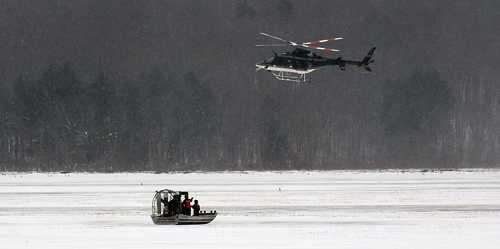 A state police helicopter hovers over the bodies of two men who died after going through the ice on snowmobiles in Tupper Lake last weekend. Forest rangers and a state police dive team used air boats to recover the bodies. (Enterprise photo — Justin A. Levine)