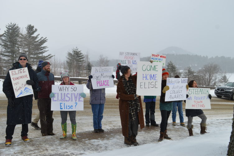 """Katie Wilson of Keene holds up a """"Come Home, Elise"""" sign at the front of a group of about a dozen protesters outside the Crowne Plaza in Lake Placid Thursday afternoon. The protesters said they were informed North Country U.S. Rep. Elise Stefanik was attending an event at the hotel at that time, but a spokesman for Stefanik did not confirm or deny several questions Thursday about whether or not she was there. (Enterprise photo — Antonio Olivero)"""