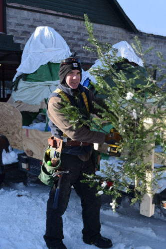 "Northern Lights School parent and board member Michael Williams attaches a tree to the school's ""mountain mosaic"" float for today's Saranac Lake Winter Carnival Gala Parade. (Enterprise photo — Chris Knight)"