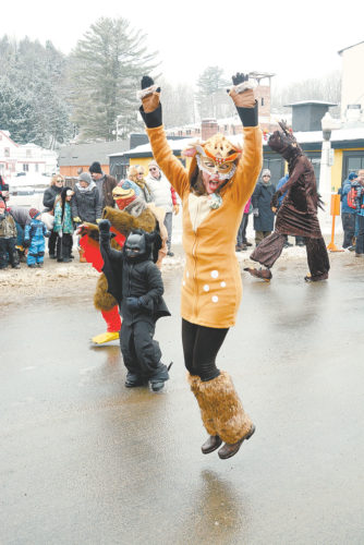 Aggie Pelletieri, dressed as a deer, jumps for joy as she marches with the Kiwanis Club of Saranac Lake float in the Saranac Lake Winter Carnival Gala Parade Saturday. Kiwanis won two trophies: one for best civic/volunteer group float and the Louis Fobare Memorial Trophy for the best float in the parade. (Enterprise photo — Lou Reuter)