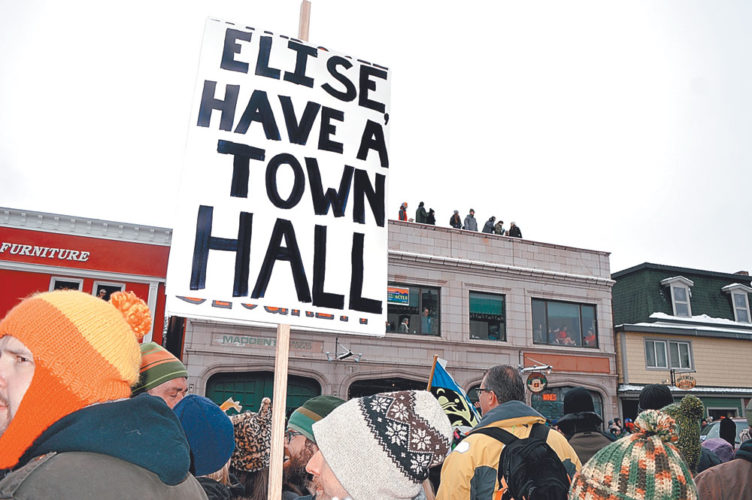 An attendee of Saranac Lake's Winter Carnival parade Saturday holds a sign asking U.S. Rep. Elise Stefanik to host a local town hall-style meeting. (Enterprise photo — Antonio Olivero)