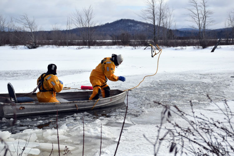 Members of the Tupper Lake Volunteer Fire Department throw a grappling hook into the Raquette River in Tupper Lake Feb. 4 in an attempt to locate a snowmobile and four-wheeler that went through the ice. (Enterprise photo — Justin A. Levine)