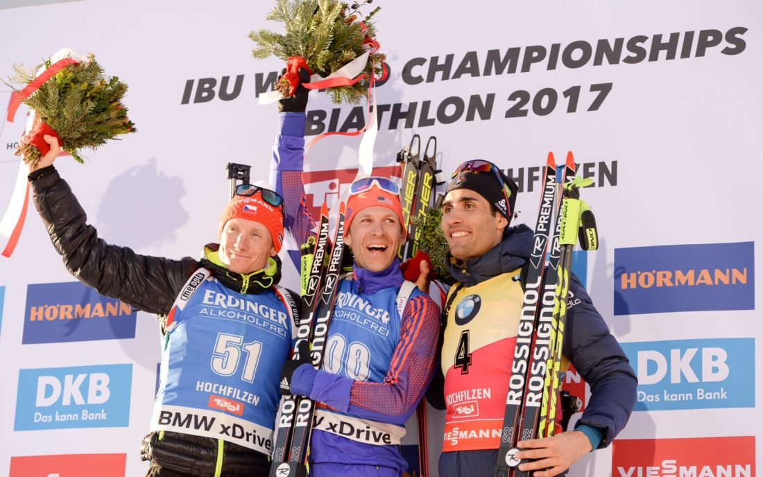 Lowell Bailey celebrates his gold-medal victory in the 20-kilometer individual race Thursday at the biathlon world championships in Hochfilzen, Austria. Ondrej Moravec of the Czech Republic, left, took silver and France's Martin Fourcade won bronze. (Photo — NordicFocus/US Biathlon)