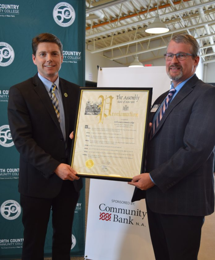 State Assemblyman Billy Jones, left, presents North Country Community College President Steve Tyrell with a proclamation honoring the college's 50 years of service to the region during a ceremony Friday in the college Connector in Saranac Lake. (Enterprise photo — Chris Knight)