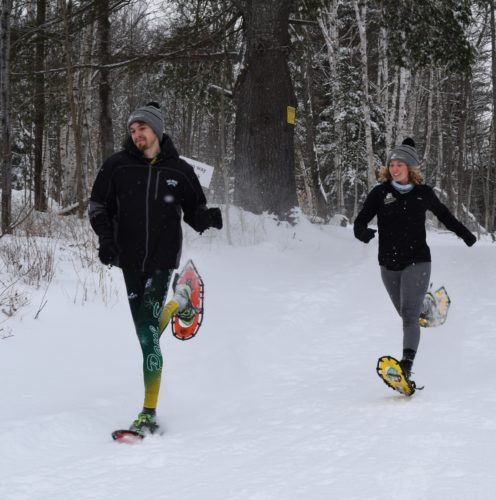 Paul Smith's College snowshoe racers Joseph St. Cyr and Chloe Matillio test out the trails at Dewey Mountain Recreation Center in Saranac Lake on Thursday in preparation for the Feb. 25 World Snowshoe Championships. (Enterprise photo — Chris Knight)