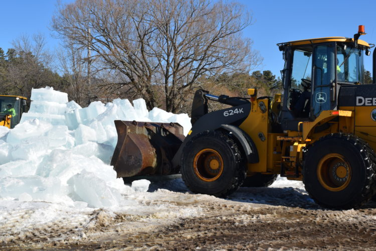 A village of Saranac Lake loader scoops up blocks from the demolished Saranac Lake Winter Carnival Ice Palace on Monday, eight days after carnival came to an end. The palace was taken down after two days of warm temperatures made it unsafe. (Enterprise photo —  Chris Knight)