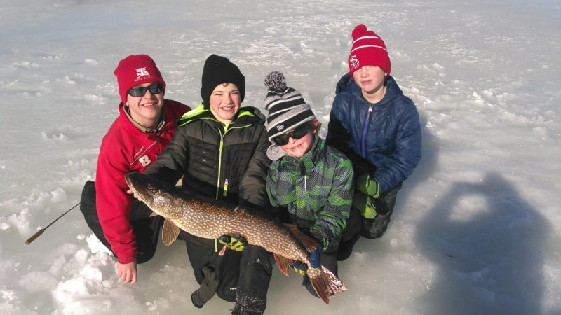 Ryan Bartholomew, second from right, of Saranac Lake, hauled in this huge northern pike while ice fishing on an unnamed Franklin County lake Monday. It measured 34 inches and weighed 10 pounds. Pictured with him, from left, are Jon Kratts, Bailey Bartholomew and Colin Rutgers. (Photo provided — Matt Bartholomew)