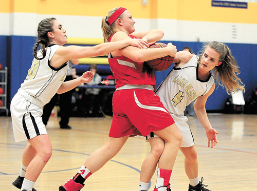 Lake Placid's Graci Daby, left, and Camile Craig attempt to wrestle the ball away from Sierra Mauro of Wells during Tuesday's playoff game on the Blue Bombers court. Mauro scored 15 points to lead the Indians to a 39-32 victory that ended Lake Placid's season. (Enterprise photo — Lou Reuter)