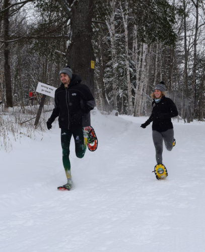 Paul Smith's College snowshoe racers Joseph St. Cyr and Chloe Matillio test out the trails at Dewey Mountain Recreation Center in Saranac Lake Feb. 16 in preparation for Saturday's World Snowshoe Championships. (Enterprise photo — Chris Knight)