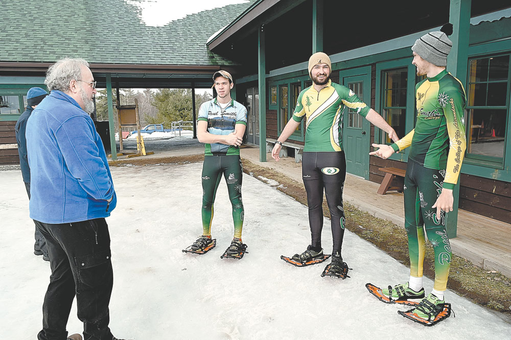 Village of Saranac Lake Trustee Rich Shapiro, left, talks Wednesday with a trio of Paul Smith's College snowshoe racers who will compete in Saturday's World Snowshoe Championships in Saranac Lake — from left, Matt Leichty, Matt Williams and Joe St. Cyr — at Dewey Mountain Recreation Center.  (Enterprise photo — Chris Knight)