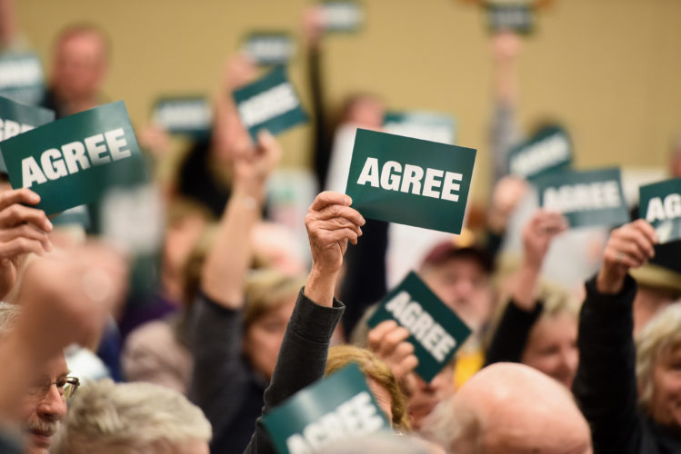"Residents of New York's 21st Congressional District hold up signs during a town hall forum Wednesday at the Crandall Public Library in Glens Falls. The signs had the word ""agree"" on one side and ""disagree"" on the other. Attendees used them to express their views when a speaker at the event offered and opinion. (Photo provided — Shawn LaChapelle, special to the Post-Star)"