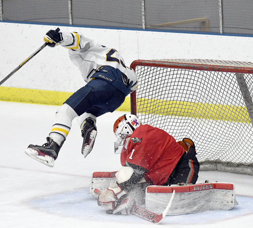 Lake Placid's Kevin Geesler goes airborne while Beekmantown goalie Cole Harvey smothers the puck during Thursday's Section VII semifinal contest at the Olympic Center's 1932 Rink. (Enterprise photo — Lou Reuter)