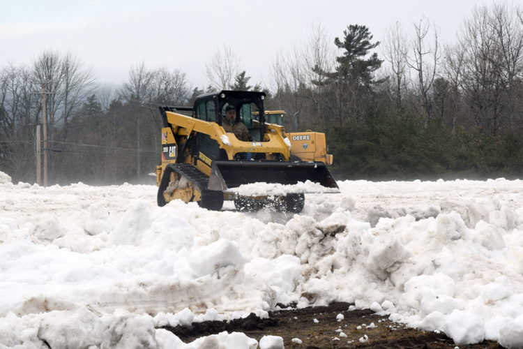 A village of Saranac Lake employee uses a mini loader Friday to move and pack down snow next to the Saranac Lake Armory on state Route 3, the start and finish area for Saturday's World Snowshoe Championships. (Enterprise photo — Chris Knight)