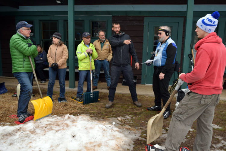 Dewey Mountain Recreation Center manager Jason Smith, center, directs shoveling volunteers near Dewey's base lodge Friday morning before they head out to help cover trails with snow for Saturday's World Snowshoe Championships in Saranac Lake. (Enterprise photo — Chris Knight)