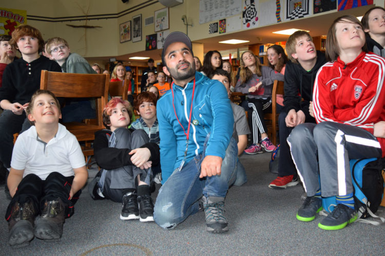 Indian snowshoe racer Tanveer Hussain, center, sits with Saranac Lake Middle School students Friday to watch a video presentation on winter recreation in the mountains of Kashmir, where he comes from. (Enterprise photo — Chris Knight)