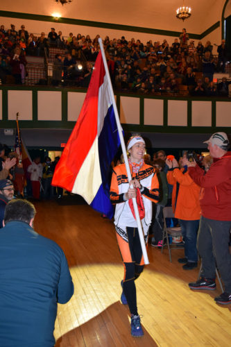 Ragna Debats of the Netherlands carries her nation's flag into the Harrietstown Town Hall auditorium during the opening ceremonies for Friday's World Snowshoe Championships in Saranac Lake. (Enterprise photo — Chris Knight)