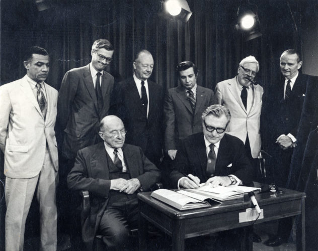 Gov. Nelson Rockefeller signs the bill creating the Adirondack Park Agency in 1971, with members of his Adirondack study commission looking on. Next to him is Harold K. Hochschild, commission chairman and founder of the Adirondack Museum in Blue Mountain Lake. (Photo provided by the Lake George Mirror)
