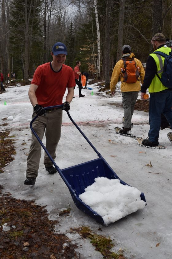 Steve Halasz of Saranac Lake hauls snow Saturday onto the World Snowshoe Championships race course at Dewey Mountain Recreation Center in Saranac Lake. (Enterprise photo -- Chris Knight)