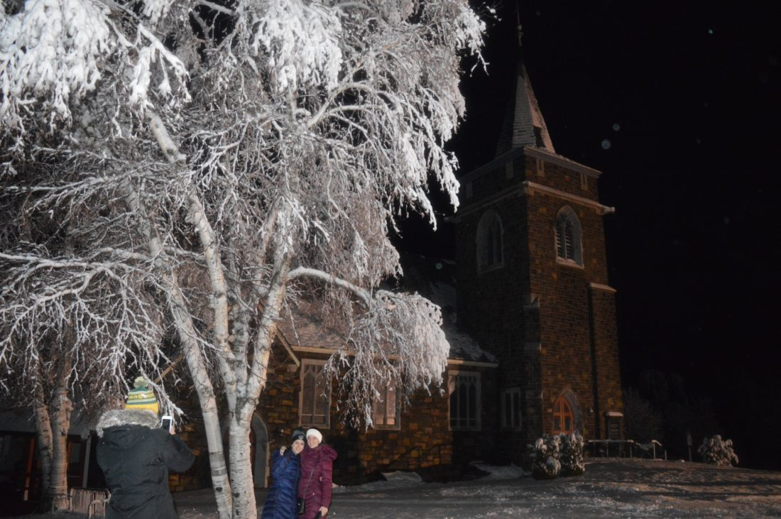 People take a photo in the snow outside the Adirondack Community Church in downtown Lake Placid Saturday night. (Enterprise photo - Antonio Olivero)