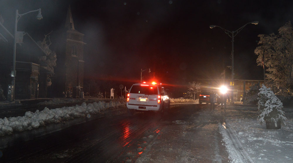 A Lake Placid Volunteer Fire Department vehicle makes its way down Main Street in Lake Placid Saturday night amid a blackout that lasted more than 19 hours.  (Enterprise photo — Antonio Olivero)