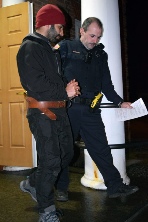 Tanveer Hussain, left, is led out of the St. Armand Town Hall Wednesday evening by Saranac Lake village Patrolman Luke Cromp. Hussain, visiting from India to race in last weekend's World Snowshoe Championships, was arraigned in town court on charges of sexual abuse and endangering the welfare of a child. (Enterprise photo — Chris Knight)