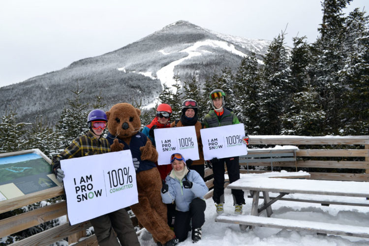 """Members of the Adirondack Youth Climate Project hold """"I Am Pro Snow, 100% Committed"""" signs at Whiteface Mountain Ski Center in Wilmington. (Photo provided by The Wild Center)"""