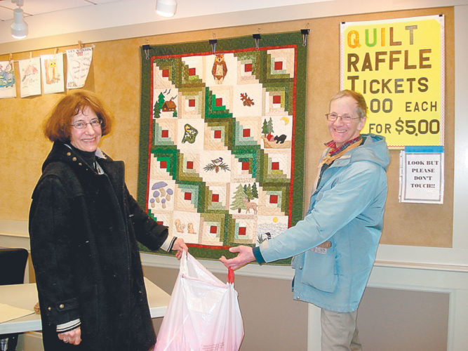 "PICKING THE WINNING TICKET — Barbara Friend and Tom Delahant assist with picking the winning ticket for ""Adirondack Splendor,"" the pieced, appliqued and hand-quilted wall hanging displayed behind them. The winner was Lisa Styles. (Photo provided — Pat Wiley)"