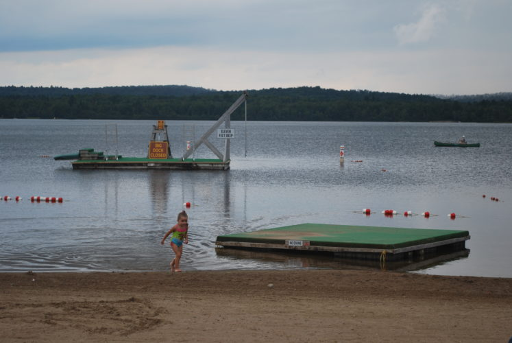 A little girl tests the water at Little Wolf Beach in TupperLake. Designers from landscape architecture firm, Terrain, unveiled what would amount to a roughly $1 million overhaul of the beach at Thursday night's TupperLake town board meeting. (Enterprise photo —Jessica Collier)