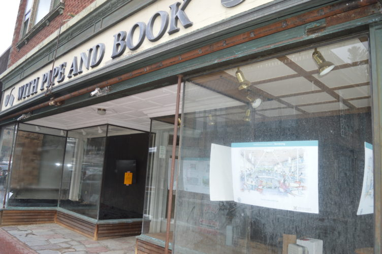 The former With Pipe and Book store at 2495 Main St. is seen Friday with renderings hung behind storefront windows of Northwood School's plans to convert the space into an educational hub after planned demolition. (Enterprise photo — Antonio Olivero)