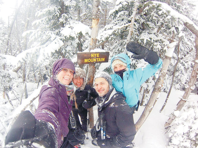 The woman attempting to break the Winter 46er speed record, Stefanie Bishop, far right, is seen Saturday at the summit of Nye Mountain along with the two local women who helped her stay on course during her hike Saturday, Elizabeth Izzo of Lake Placid, second from left, and Brittany Friedrich, far left, and their friend Jake. (Photo provided — Brittany Friedrich)