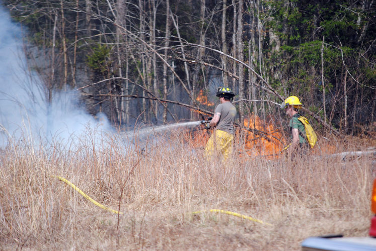 Firefighters hose down a wildfire north of Tupper Lake on May 4, 2015. Fire officials said at the time they thought the blaze was caused by people burning things at a remote hunting camp, even though a statewide burn ban was on at the time and it was a dry, windy day. (Enterprise photo — Tom Salitsky)