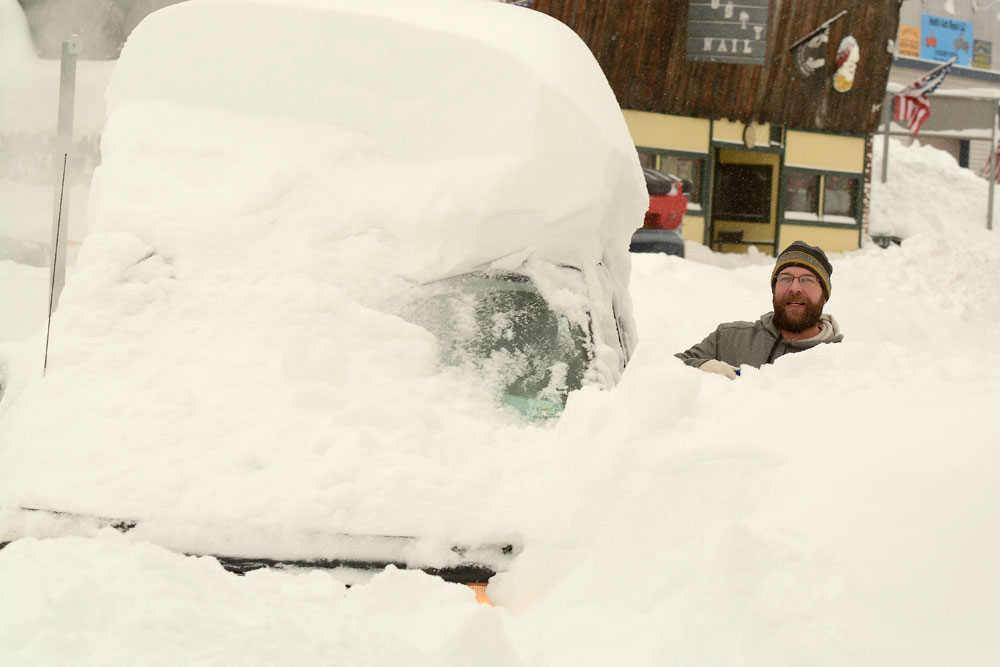 Surrounded by neck-deep snow, Scott Young digs out his van around 8 a.m. today in the parking lot next the No. 1 Chinese Restaurant in Saranac Lake. (Enterprise photo — Lou Reuter)