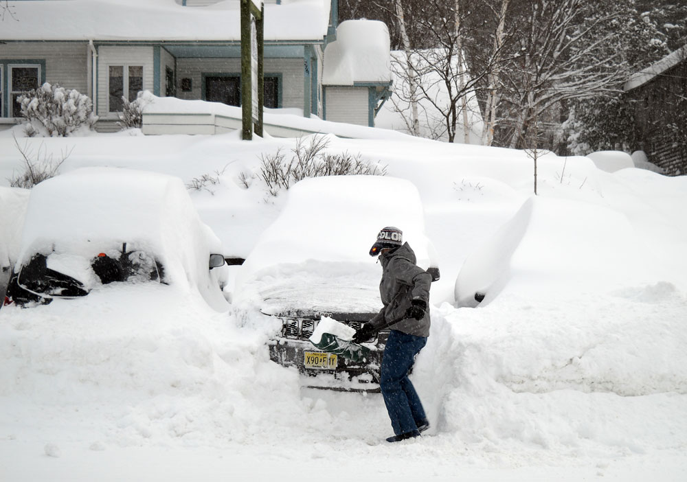 Mike Martineau of Lake Placid shovels out his car Wednesday morning. He said he cleared 7 inches of new snow after previously clearing his car at 7 p.m. Tuesday. (Enterprise photo — Antonio Olivero)