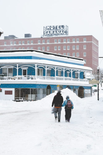 Two people walk up a desolate Broadway in Saranac Lake Wednesday near a pile of snow in the middle of the street. The village's downtown was closed for most of the day so village crews could remove snow from the streets and sidewalks. (Enterprise photo — Chris Knight)