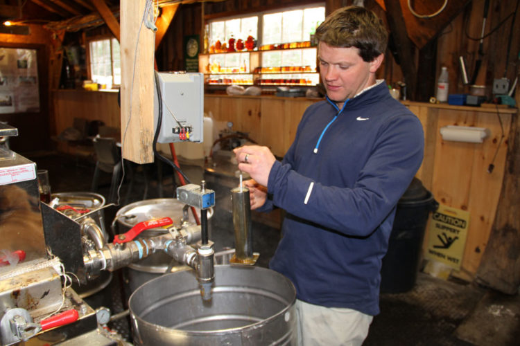 Michael Farrell, head of Cornell University's Uihlein Forest Sugarhouse in Lake Placid, tests the sugar content of a batch maple syrup there in March 2016. (Enterprise photo — Andy Flynn)