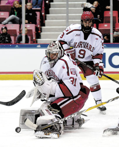 Harvard goalie Merrick Madsen makes a pad save during the third period of Friday's ECAC semifinal game against Quinnipiac at the Olympic Center in Lake Placid. Madsen recorded 25 saves to pace the Crimson defense, and teammate Sean Malone netted a hat trick as Harvard defeated the Bobcats 4-1 to advance to tonight's championship game against Cornell. (Enterprise photo — Lou Reuter)