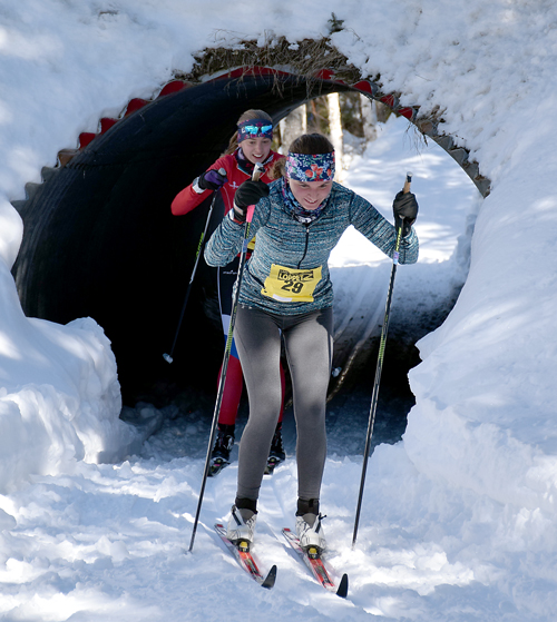 Nina Armstrong, of Lake Placid, leads Lucy Hochschartner out of the tunnel during the Loppet's 50-kilometer classic race Saturday at Mount Van Hoevenberg. Armstrong finished second overall with a time of 3:27:30.5, while Hochschartner was third in 3:27:31. (Enterprise photo — Justin A. Levine)