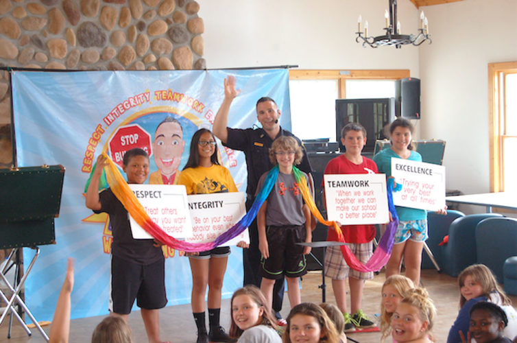A sheriff's deputy conducts a character education workshop with a group of happy campers. (Photo provided)