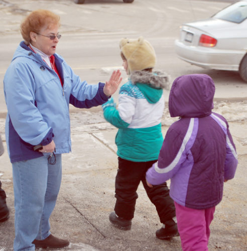 Saranac Lake Interfaith Food Pantry coordinator Anne Cooney gives high-fives to Petrova Elementary School students after they dropped off donations to the pantry. (Enterprise photo — Chris Knight)