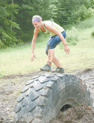 A Warrior Run athlete makes her way across one of the obstacles at Big Tupper Ski Area in Tupper Lake in July 2016. This year, the Warrior Run will move to a course inside the village.  (Enterprise photo — Justin A. Levine)
