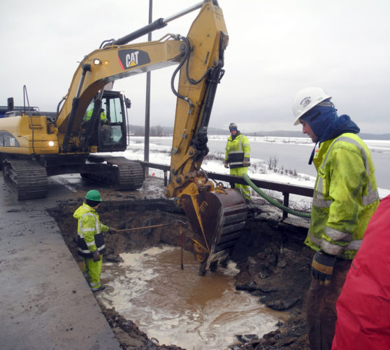 Workers try to find and repair a water line break while using a Vac-Con truck to suck water out of a hole dug in state Route 30 in Tupper Lake Friday afternoon. (Enterprise photo — Ben Gocker)